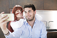 Playful couple in kitchen taking a selfie - ZEF002647