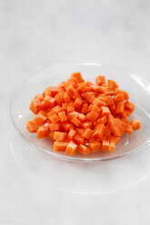 Glass bowl of diced carrots on white ground - EVGF001033