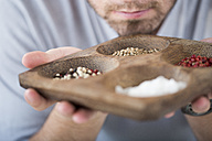 Man holding a bowl and smelling spices - ZEF002671