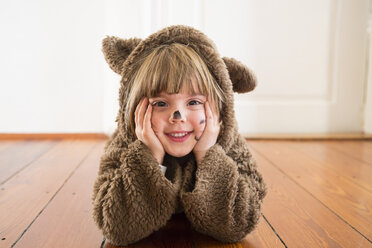 Portrait of happy little girl masquerade as a bear lying on wooden floor - LVF002451