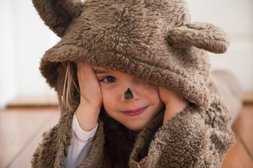 Portrait of smiling little girl masquerade as a bear lying on wooden floor - LVF002454