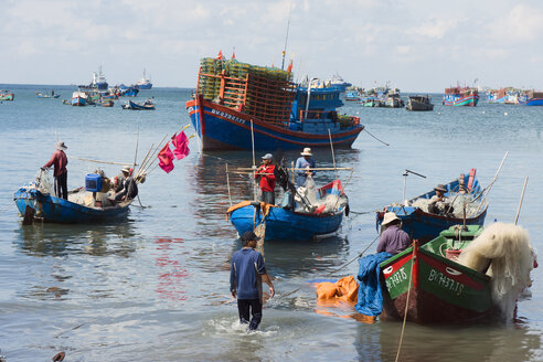 Vietnam, Vung Tau, fishermen sorting nets in harbor - WE000318