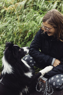 Smiling young woman communicating with her Border Collie - DWF000217