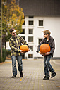 Two boys carrying two big pumpkins - PAF001091