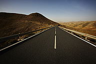Spain, Canary Islands, Fuerteventura, view to empty road at landscape - STKF001106
