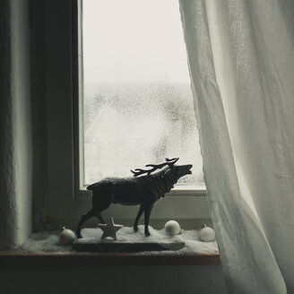 Belling stag statuette with christmas decoration and artificial snow in front of window, Vaihingen/Enz, Baden-Württemberg, Germany - SBD001559