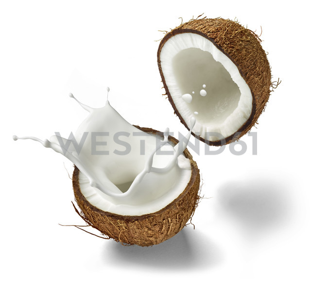 Two halves of a coconut and splashing coconut milk in front of white background - RAMF000029