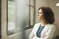 Young businesswoman looking out of window - UUF002858