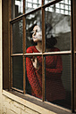 Young woman looking out of window - UUF002879