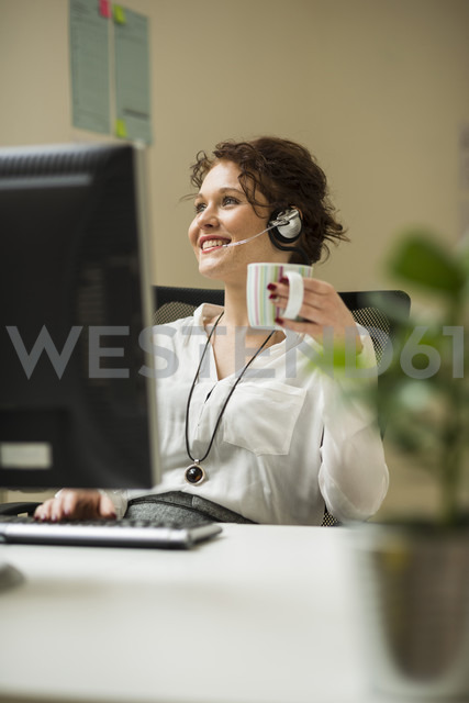 Smiling young woman in office wearing headset - UUF002912