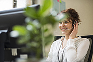Smiling young woman in office wearing headset - UUF002914