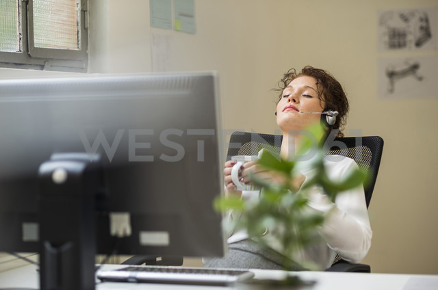 Young woman in office wearing headset leaning back - UUF002918