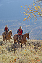 USA, Wyoming, Big Horn Mountains, riding cowgirl and cowboy in autumn - RUEF001299