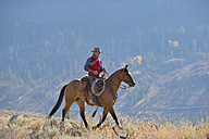 USA, Wyoming, Big Horn Mountains, riding cowboy in autumn - RUEF001303