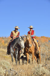 USA, Wyoming, Big Horn Mountains, cowboy and cowgirl on her horses in autumn - RUEF001341