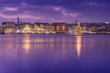 Germany, Hamburg, Downtown skyline with illuminated Christmas tree on Alster river - NKF000208