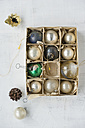 Cardboard box of old glass Christmas baubles on white ground - MYF000770