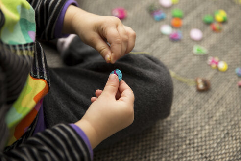Girl playing with hand made buttons - MIDF000011