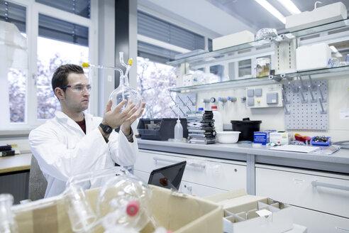 Chemist working in lab holding round bottom flask - SGF001244