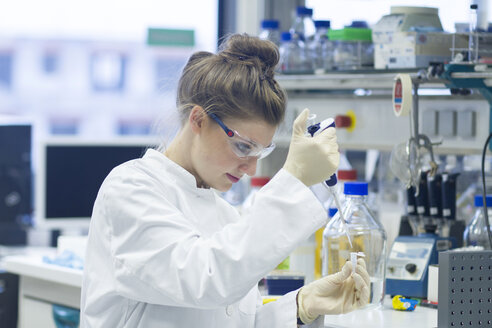 Biologist working in laboratory with pipette - SGF001257