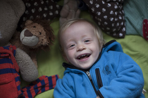 Portrait of laughing little boy lying on bed with soft toy - RB002192