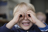 Portrait of smiling little boy looking through his hands formed like spectacles - RB002212