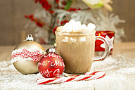 Christmas baubles, sugar cane and glass of hot chocolate with cream and marshmallows on artifical snow - JUNF000122