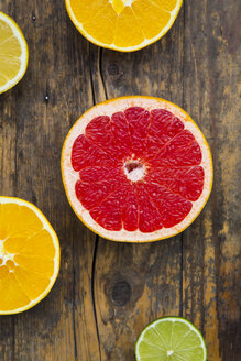 Slices of different citrus fruits on dark wood - LVF002478