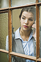 Young businesswoman on cell phone looking out of window - UUF002999