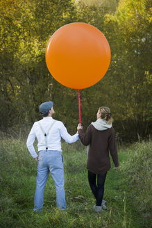 Couple standing with balloon on meadow - JTLF000019