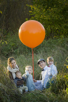 Family sitting with balloon on meadow - JTLF000014