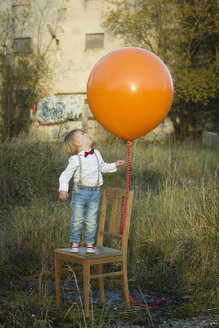 Boy standing on chair with balloon on meadow - JTLF000009