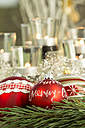 Christmas decoration, Red christmas baubles and candles in the background - JUNF000137