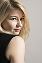 Portrait of blond woman viewing over her shoulder - UU003014
