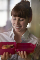 Smiling woman holding lunch box - STKF001133