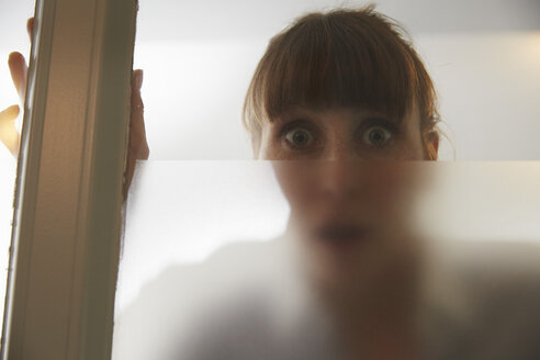 Frightened woman behind glass pane - STKF001135