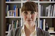 Portrait of woman in front of book shelf - STKF001141