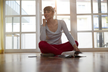 Woman sitting on floor with magazine - STKF001147