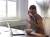 Smiling woman with laptop at desk on the phone - STKF001186