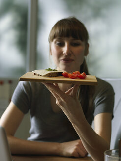 Woman at desk holding board with snack - STKF001171