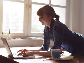 Smiling woman at desk using laptop - STKF001166