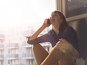 Happy woman at open window on cell phone - STKF001164