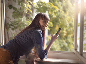 Smiling woman at open window holding cell phone - STKF001160