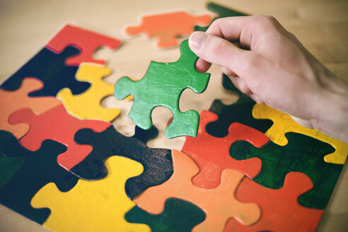 Hand holding up a large puzzle piece on a table - MF001347