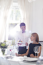 Waiter serving dinner to woman in elegant restaurant - WESTF020415