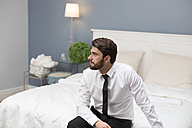 Serious man in shirt and tie sitting on bed - WESTF020451