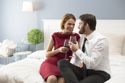 Affectionate couple holding wine glasses in bedroom - WESTF020454