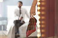 Woman holding high heels with man in bedroom - WESTF020460
