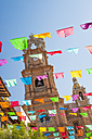 Mexico, Jalisco, Puerto Vallarta, Colorful flags, Tower of the Church of Our Lady of Guadalupe in the background - ABAF001597