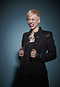Portrait of aggressive young blond woman dressed in black in front of blue background - RHF000473